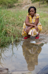 Portrait of Phyllis next to some water within the slum area which the community use for washing. The water has been conatminated by the factory. Photo: Goldman Environmental Prize