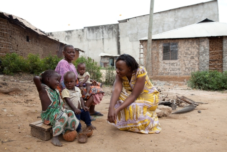 Phyllis talking with children from the community who are suffering from lead poisoing. In the background is the wall to the factory which is located right next to the family's home. The children play in the dirt next to the factory wall - the soil is contaminated. Photo: Goldman Environmental Prize